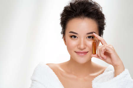 Woman holds ampoule with serum for hair or skin care. Photo of asian woman after shower on white background. Beauty and skin care concept 版權商用圖片