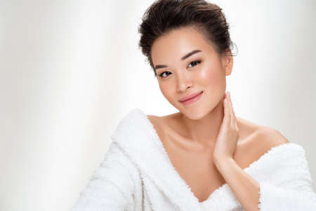 Beautiful woman after shower. Photo of asian woman with perfect makeup on white background. Beauty and skin care concept