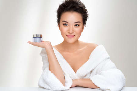 Woman holds jar with cosmetic cream. Photo of asian woman after shower on white background. Beauty and skin care concept