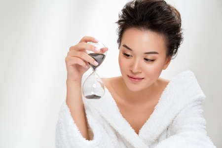 Woman holds hourglass. Photo of asian woman with perfect makeup on white background. Beauty and skin care concept