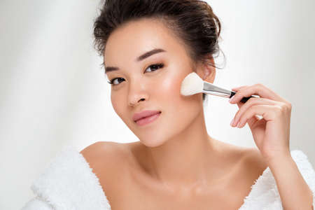 Woman applying rouge on the face using makeup brush. Photo of asian woman after shower on white background. Beauty and skin care concept