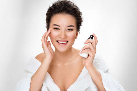 Beautiful woman applying moisturizer cream on her face. Photo of asian woman after shower on white background. Beauty and skin care concept 免版税图像