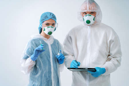 Doctor holds clipboard and nurse holds an injection syringe and vaccine. Healthcare workers in protective suits and medical masks 免版税图像