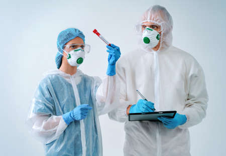 Doctor holds clipboard and nurse shows blood test result. Healthcare workers in protective suits and medical masks 免版税图像