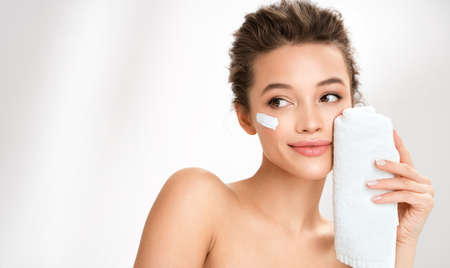 Woman wiping facial skin with towel, removing cream. Photo of woman with perfect skin on white background. Beauty and skin care concept 免版税图像