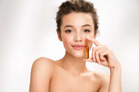 Woman holds ampoule with serum for hair or skin care. Photo of attractive woman with perfect makeup on white background. Beauty concept 免版税图像