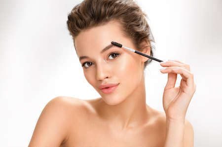Young girl using brush for eyebrows. Photo of girl with perfect makeup on white background. Beauty and skin care concept 免版税图像