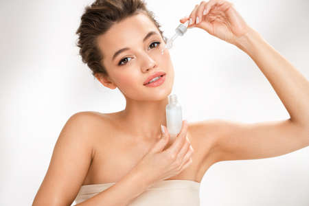 Woman applying hyaluronic serum on her face with pipette. Photo of attractive woman with perfect makeup on white background. Beauty concept