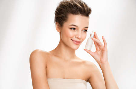 Woman holds hyaluronic serum. Photo of attractive woman with perfect makeup on white background. Beauty concept