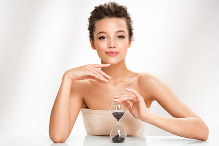 Woman holds hourglass. Photo of beautiful woman with perfect skin on white background. Beauty and skin care concept