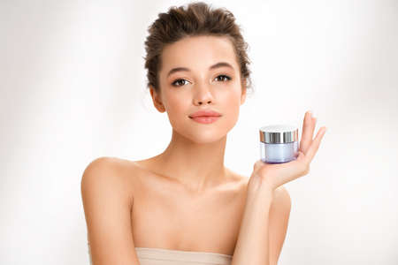 Woman holds jar with cosmetic cream. Photo of woman with perfect skin on white background. Beauty and skin care concept