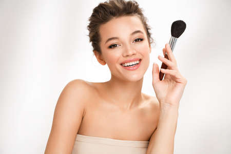 Woman with makeup brush. Photo of woman with perfect makeup on white background. Beauty concept 免版税图像