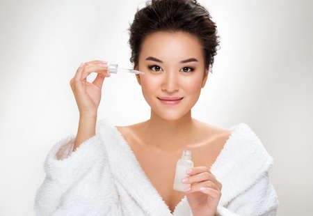 Woman holds bottle with serum for skin care. Photo of asian woman after shower on white background. Beauty and skin care concept