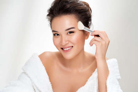 Woman applying powder on the face using makeup brush. Photo of asian woman after shower on white background. Beauty and skin care concept