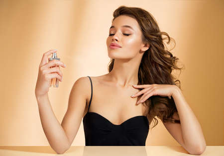 Woman with bottle of perfume. Photo of woman with perfect makeup on beige background. Beauty concept 免版税图像