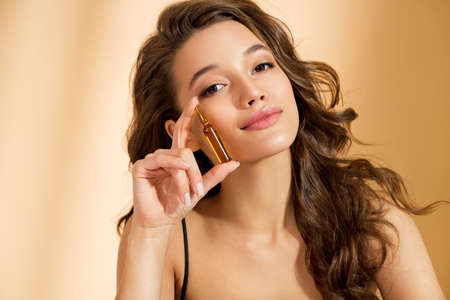 Woman holds ampoule with serum for hair or skin care. Photo of attractive woman with perfect makeup on beige background. Beauty concept