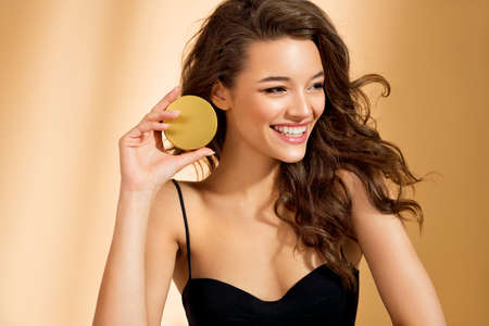 Woman holds jar with cosmetic cream. Photo of attractive woman with perfect makeup on beige background. Beauty concept