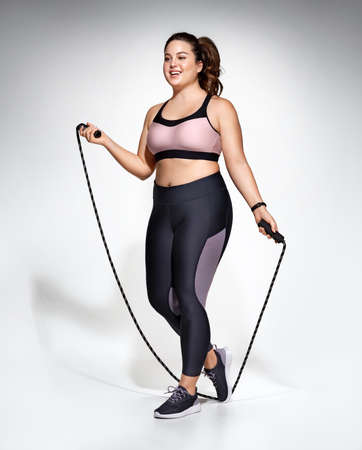 Sporty girl with skipping rope. Photo of model with curvy figure in fashionable sportswear on gray background. Sports motivation and healthy lifestyle Stockfoto
