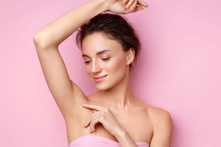 Young woman holding her arm up and showing clean underarm. Photo of smiling woman with smooth skin after epilation on pink background. Beauty concept