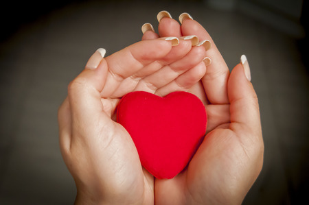 Young womans hands holding a little heart abstract image.
