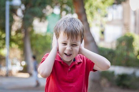 outcry: Stressed out little 5-year old Caucasian little boy outside closing his ears and screaming of pain, trauma, traumatic experience and loud noise stock image. Autism, autistic child, asperger syndrome Stock Photo