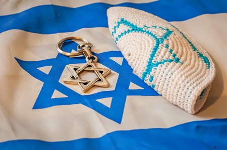 zionism: Folded Jewish customary kippah cap, a Star of David on the unfolded Flag of Israel. Judaism vs. Zionism concept. Israel Independence Day, Yom Hazikaron, Yom HaAtzmaut.