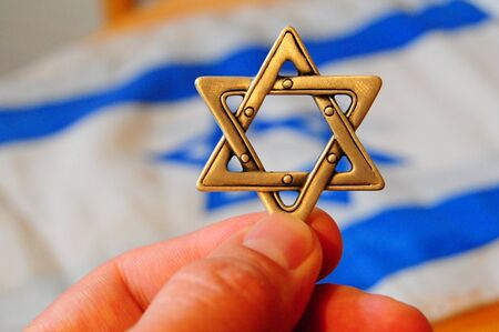 jewish community: Fingers holding a Jewish star hexagram with Israeli flag on the background. Zionism concept. Israeli citizenship, passport Stock Photo