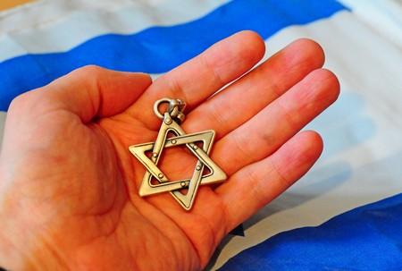 이스라엘 유태인 스타의 데이비드 스타 배경에 들고 손을.