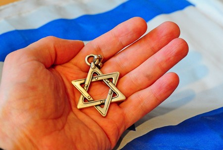 Hand holding a Jewish Star of David with Israel flag on the background.