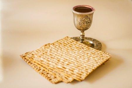 """Joodse feestdagen: Paasfilet (Pesach) matzah en een zilveren kop vol wijn met een traditionele zegen """"Borei Pri HaGafen"""" gegraveerd. Stockfoto"""