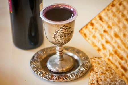 Jewish holidays: Passover (Pesach) matzah, bottle of red wine and a silver cup full of wine with a traditional blessing Borei Pri HaGafen engraved on it.