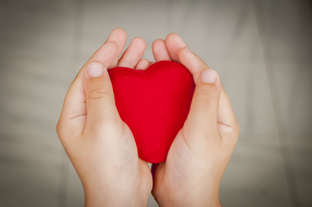 sincerity: Child holds a big red heart in his hands. Sincerity, sincere love stock image.