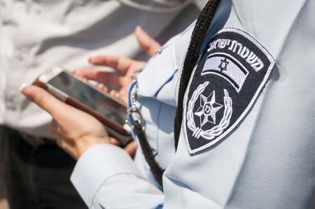 Israeli female police officer with an emblem on her uniform holding cellular phone in her hands. Stock photo image illustration. Tel Aviv, Israel, April 2014. Editorial