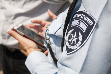 Israeli female police officer with an emblem on her uniform holding cellular phone in her hands. Stock photo image illustration. Tel Aviv, Israel, April 2014. Editoriali