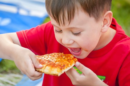 Cute little Caucasian kid eating pizza. Hungry child taking a bite from pizza on a pizza party.