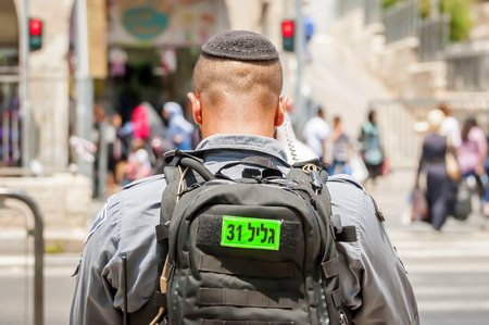 kippah: JERUSALEM, ISRAEL. June 20, 2017. Israel Border Police officer looking at the street pedestrian crossing near the terror attack site at the Damascus gate. Israeli-Palestinian conflict stock image.