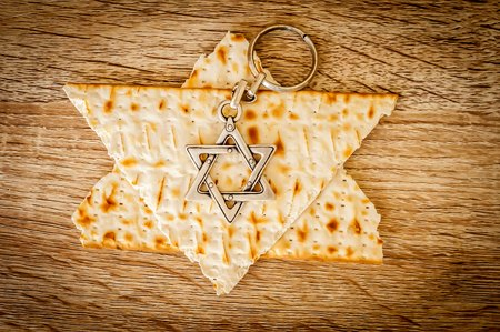 Two pieces of matzah make up a Jewish Star of David (Magen David) with a Jewish key chain metal hexagram star. Pessach stock image, Jewish Passover holiday.