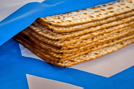 A pile of traditional Jewish Passover matzah unleavened bread wrapped in the flag of Israel. Pesach concept, Jewish tradition.