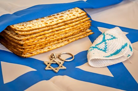 Matzah, traditional Jewish unleavened bread, wrapped up in a flag of Israel. David Star (Magen David), Pesach concept, Jewish Passover stock image. Stock Photo
