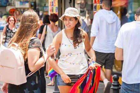 TEL AVIV, ISRAEL. June 9, 2017. Girl selling LGBT rainbow flags in the street at the Gay Pride Parade in Tel Aviv 2017.