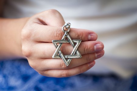 Young womans hand holding a Star of David (
