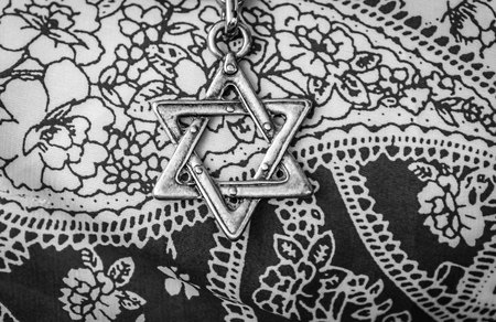 A Star of David, famous Jewish hexagram symbol, on a black and white  flower background.