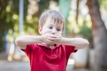 Caucasian little 4-year old boy closing his mouth with hands. Secrecy or stuttering stock image. Speech therapist, speech problems, stammering, stammer, speech impediment, mumble, mumbling. therapy Stock fotó