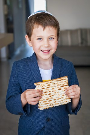 Cute Caucasian child in a yarmulke holding a piece of traditional Jewish matzo unleavened bread in a room.