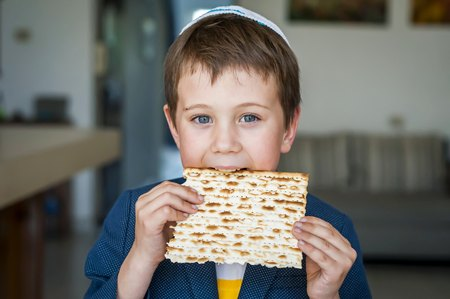 Cute Caucasian child in a yarmulke taking a bite from a traditional Jewish matzo unleavened bread in a room.