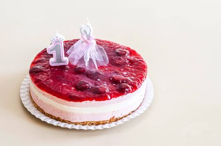 Sweet white and pink mousse cake with several layers and strawberry jam topping with a 1 year old birthday candle and a ballet dancer candle. One year old birthday party celebration concept image. 版權商用圖片
