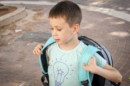 Nettes 7-jähriges kaukasisches Kind, das lacht und erwartet, am 1. September zum ersten Mal zur Schule zu gehen. Glückliches Kind des ersten Mals voller Erwartungen, freut sich. Zurück zum Schulkonzept. Standard-Bild