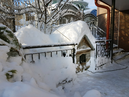 Wooden doghouse on the background of snow in winter