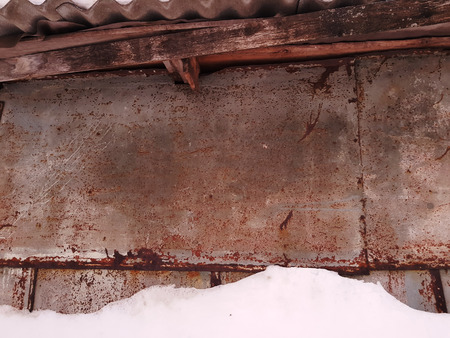 The texture of a very old wall in the winter on the background of snow