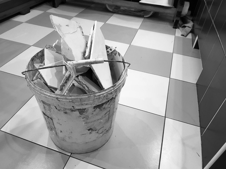 Repair construction and debris in a bucket with pieces of tile and plasterboard on the tiled floor